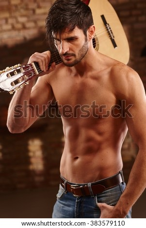 Sexy latin lover holding guitar with bare upper body.