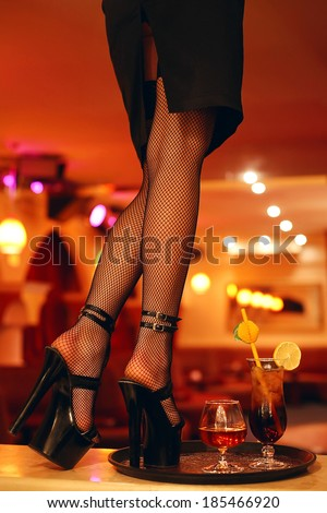 Sexy legs of a waitress standing on the bar with a cocktail. Copy-space. Indoor shot - stock photo