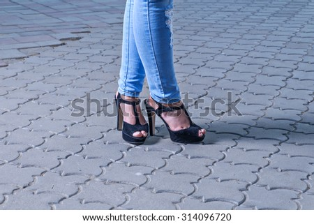 Sexy legs of fashionable girl on paved footpath. Closeup of young woman legs on cobblestoned street. Slim legs of young fashion women in tight jeans standing on high heels outdoors. - stock photo