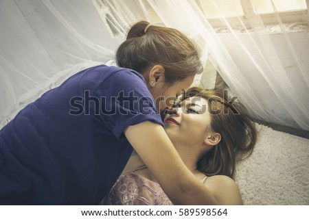 Lesbians kiss in bed