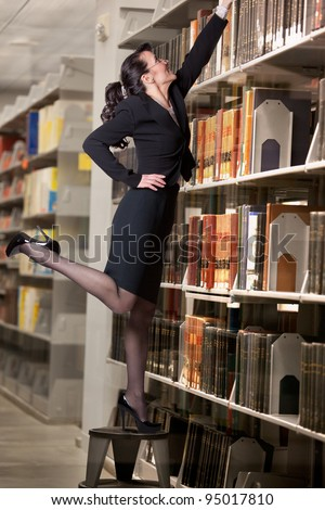 Sexy librarian reaching for a book high on a shelf