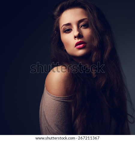 Sexy long hair woman with hot pink lips on dark shadows background looking with passion look. Art color portrait