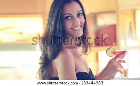 Sexy long haired woman drinking a cocktail at the bar