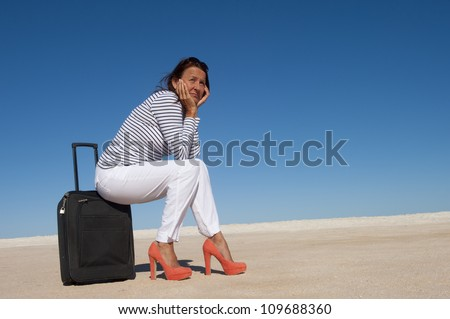 Sexy looking mature woman sitting lost in a remote desert area on a suitcase, looking for a transport to travel, isolated with blue sky as background and copy space..