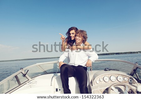 Sexy lovely couple on the luxury boat in open sea in summer. Young man and sensual brunette outdoor portrait in classic dress. Outdoors, lifestyle.