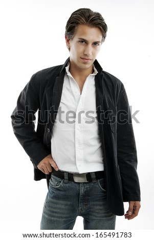 Sexy macho handsome young man in trendy jeans and jacket standing with a confident pose and his hand on his hip, three quarter on white
