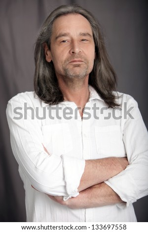 Sexy macho middle-aged man with shoulder length hair and a stubbly beard standing with his arms folded and an amused expression looking at the camera