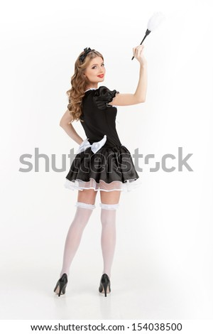 Sexy maid. Rear view of beautiful young maid in white pantyhose holding brush and looking over shoulder - stock photo