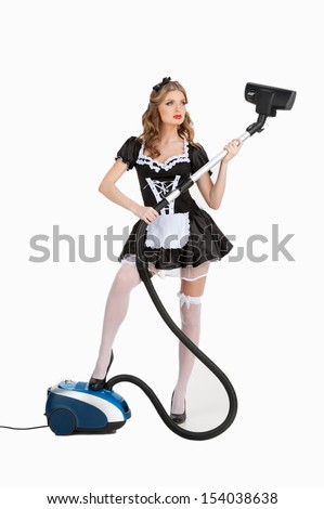 Sexy maid with vacuum cleaner. Beautiful young maid in white pantyhose holding vacuum cleaner while standing isolated on white - stock photo