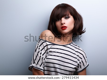Sexy makeup short hair woman in casual clothes posing on blue background with empty copy space