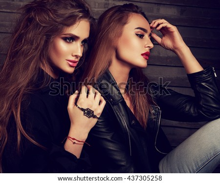 Sexy makeup two beautiful models  sitting in profile on street wall background. Closeup fashion portrait