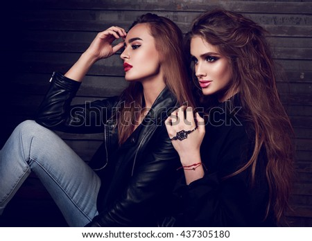 Sexy makeup two beautiful women sitting in profile on street wall background. Dark fashion portrait