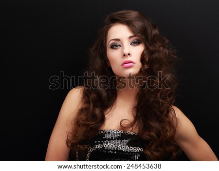 Sexy makeup woman with long curly hair looking on black background