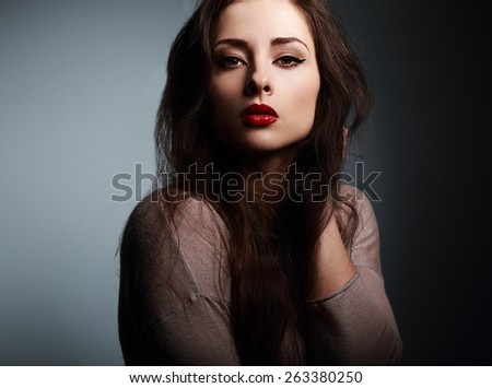 Sexy makeup woman with red lipstick looking on dark shadows background - stock photo