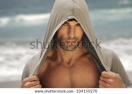 Sexy male model outdoors wearing a hooded shirt and revealing his chest - stock photo