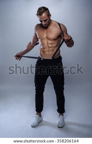 sexy male model with braces and jeans with sixpack posing topless - stock photo