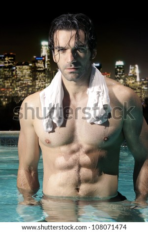 Sexy male model with great abs and muscular body in swimming pool at night with city skyline background - stock photo