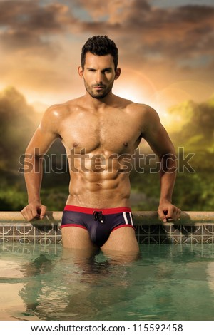 Sexy male model with great body and abs in pool - stock photo