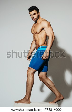 Sexy male muscular model in blue sportwear on white background with shadow - stock photo