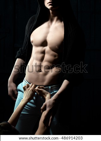 Sexy male torso with female hands on muscular body of young man
