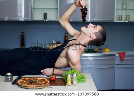 sexy man chef in the kitchen eating grape - stock photo