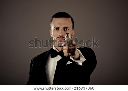 Sexy man gangster agent criminal police in a tuxedo pointing a gun - stock photo