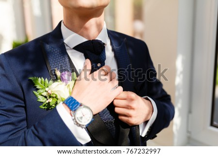Sexy man in an expensive luxury blue suit straightens his shirt sleeves and cuffs. Closeup dressed in a blue jacket and white shirt and vest, expensive watch in the hotel lobby