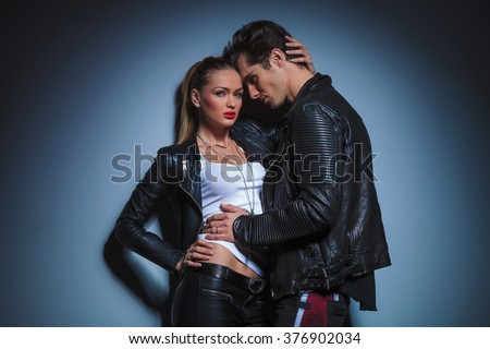 sexy man in leather jacket leans against his busty girlfriend that poses touching his head in studio  - stock photo