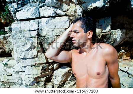 Sexy man posing on stones background - stock photo