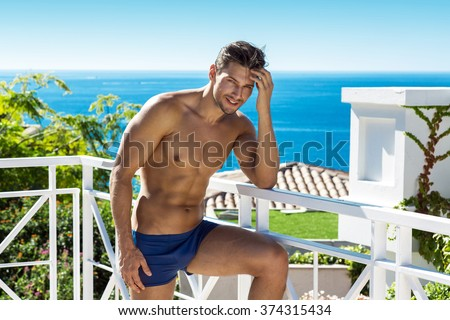 Sexy man wear swimming trunks posing in sea scenery - stock photo