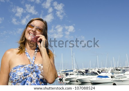 Sexy mature woman enjoying a relaxed sunny day out at a marina, talking on mobile phone, with boats as background, isolated with blue sky as copy space. - stock photo