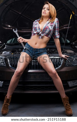 Sexy mechanic. Full length of beautiful young woman holding big wrench and looking at camera while leaning at the car in auto repair shop - stock photo