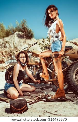 Sexy mechanic girls are repairing old motorbike on the desert background. - stock photo