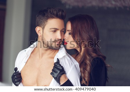 Sexy milf woman undress young macho lover indoor - stock photo