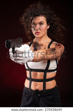 Sexy military, killer woman posing with gun. With dirty face, blood and wound.  - stock photo