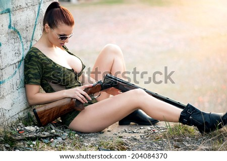 Sexy military woman model with weapon - stock photo