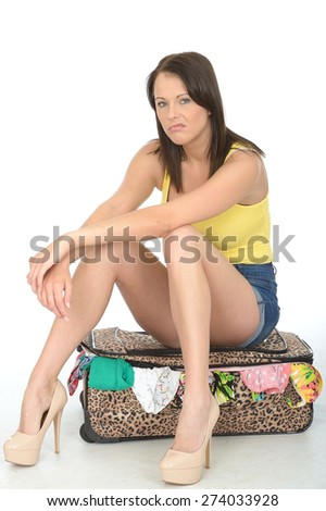 Sexy Miserable Fed Up Young Woman Sitting on a Suitcase Resting on Her Knees Looking Unhappy - stock photo