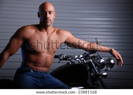 Sexy mixed race man wearing jeans and no shirt sitting on a motor cycle.