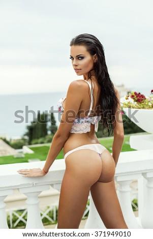 Sexy model in bikini posing in summer scenery - stock photo