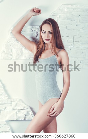 Sexy model in the tankini. Studio shot with white brick wall on the background