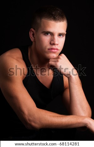 sexy model male with black shirt on a black background - stock photo