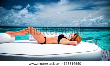 Sexy model with perfect body lying down on big white lounger on the beach and taking sunbath, luxury summer holidays, pleasure and enjoyment concept - stock photo