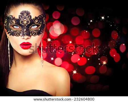 Sexy model woman in venetian masquerade carnival mask at party over holiday glowing red background. Christmas and New Year celebration. Glamour lady - stock photo