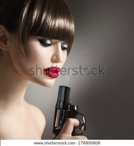 Sexy model woman with a gun. Beauty girl portrait, beautiful lady with revolver. Perfect makeup and fringe hairstyle, red lips - stock photo