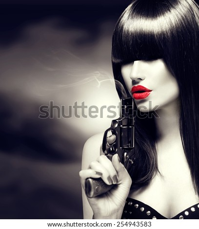 Sexy model woman with a gun. Black and white portrait of beauty lady with revolver. Perfect makeup and fringe hairstyle, red lips