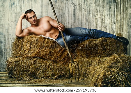 Sexy muscular cowboy lying on a haystack. Western style. - stock photo