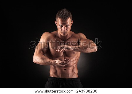Sexy muscular guy in the studio shows the various movements
