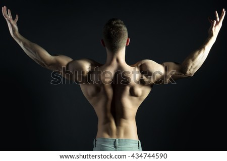 Sexy muscular male back of athlete bodybuilder posing in power with raised hands and bare torso on dark background