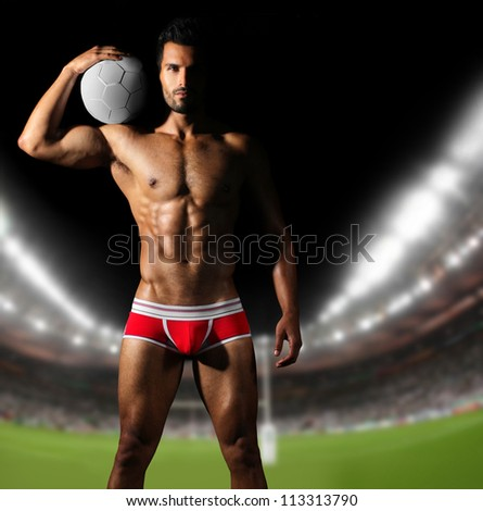 Sexy muscular man as soccer player in red underwear holding ball on field in crowded stadium - stock photo
