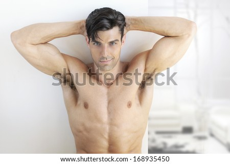 Sexy muscular man in bright modern interior - stock photo